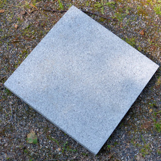 Harmaa graniittilaatta, väri on hyvin vaalea. Pinta on hakattu tai poltettu ja se tarjoaa hyvän otteen paljaalle jalalle.